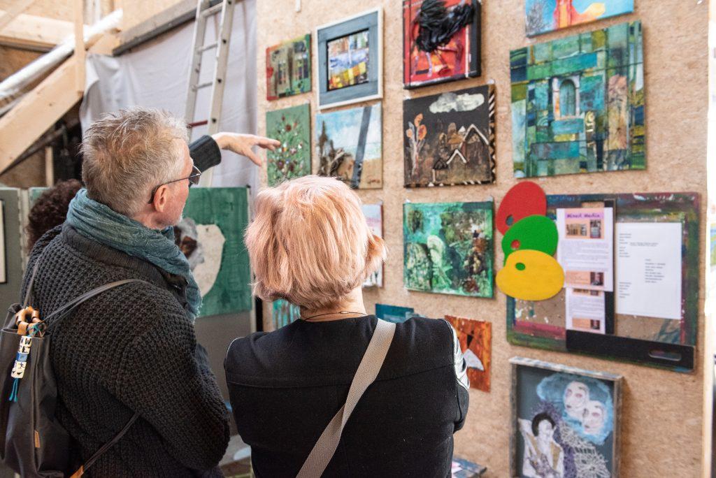Docent Wim Mecking toont een bezoeker de werken die zijn gemaakt in zijn cursus Mixed Media.